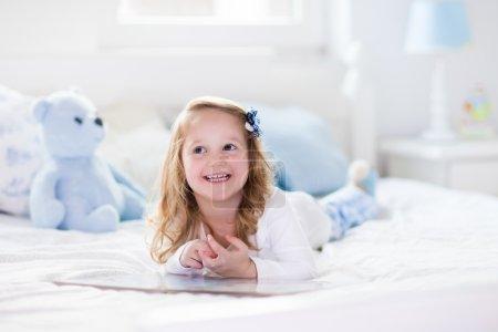 Photo pour Fille de drôle heureux bambin lisant un livre et en jouant avec son ours en peluche jouet dans son lit. Enfants jouer à la maison. Pépinière blanc. Enfant en chambre ensoleillée. Enfants lire et d'étudient. Intérieur pour bébé et jeune enfant. - image libre de droit
