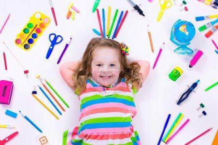 Littel girl with school supplies