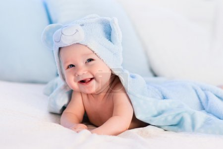 Baby boy in blue towel on white bed
