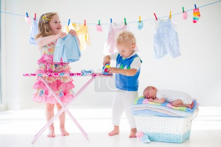 Kids ironing clothes for baby brother