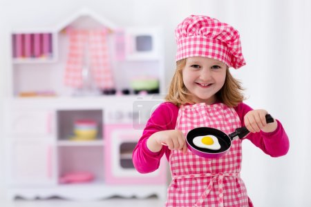 Little girl playing with toy kitchen