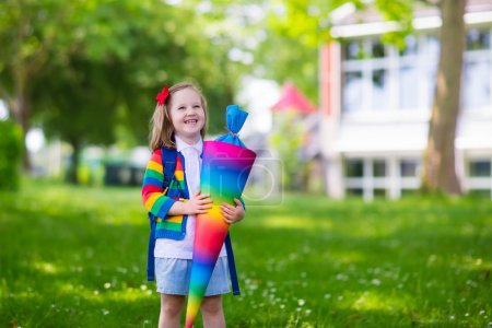 Little child with candy cone on first school day