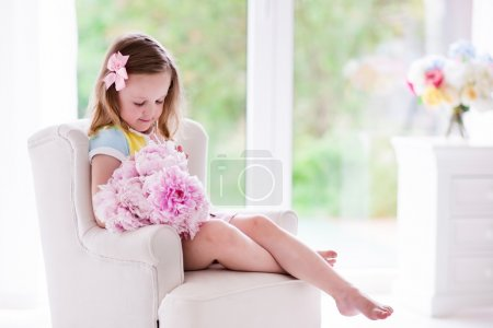 Little girl with peony flowers in white bedroom
