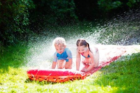 Children playing with garden water slide