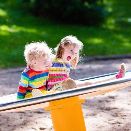 Foto de Pequeño niño y una niña en un parque infantil. Niño jugando al aire libre en verano. Los niños jugar en el patio de la escuela. Niño feliz en el jardín de infantes o preescolar. Tierra del juego de los niños que se divierten en la guardería. Niño en un columpio. - Imagen libre de derechos