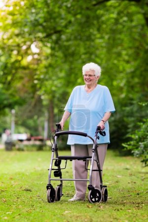 Photo for Happy senior handicapped lady with a walking disability enjoying a walk in a sunny park pushing her walker or wheel chair, aid and support during retirement concept. - Royalty Free Image