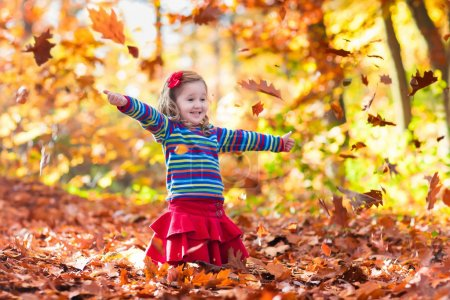 Photo for Happy little girl playing in beautiful autumn park on warm sunny fall day. Kids play with golden maple leaves. - Royalty Free Image