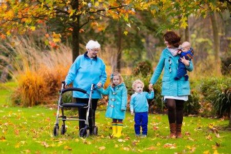 Photo pour Heureuse dame âgée avec une marchette ou un fauteuil roulant et des enfants. Grand-mère et les enfants profitent d'une promenade dans le parc. Enfant subvenant aux besoins des grands-parents handicapés. Visite de famille. Générations amour et relation . - image libre de droit