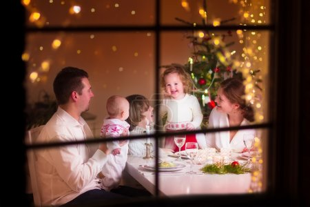 Photo for Young big family celebrating Christmas enjoying dinner, view from outside through a window into a decorated living room with tree and candle lights, happy parents eating with three kids - Royalty Free Image