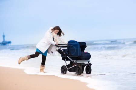 Happy active young mother walking on a beach pushing an all terrain double stroller