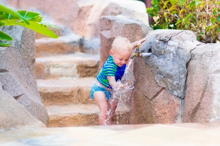 Baby boy playing with water tap outdoors