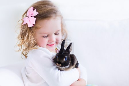 Photo for Happy laughing little girl playing with a baby rabbit, hugging her real bunny pet and learning to take care of an animal. Child on a white couch at home or kindergarten. - Royalty Free Image
