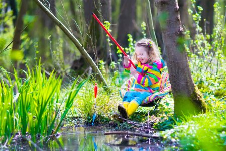 Photo for Child playing outdoors. Preschooler kid catching fish with red rod. Little girl fishing in forest river in summer. Adventure kindergarten day trip in wild nature, explorer hiking and watching animals. - Royalty Free Image