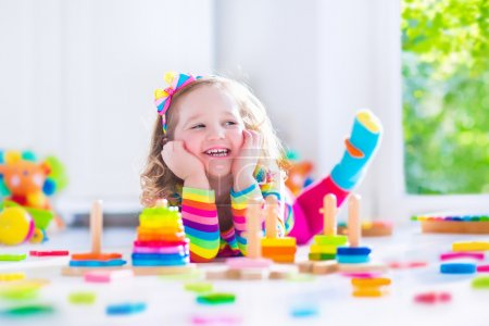 Photo for Child playing with wooden toys at preschool. Cute toddler girl having fun with toy blocks, building a tower at home or day care. Educational kids toy for nursery or kindergarten. - Royalty Free Image