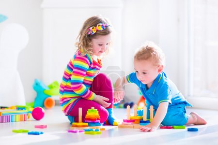 Photo for Kids playing with wooden toys. Two children, cute toddler girl and funny baby boy, playing with toy blocks, building towers at home or day care. Educational child toys for preschool and kindergarten. - Royalty Free Image