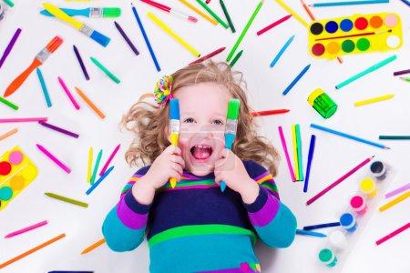 Littel girl with school art supplies
