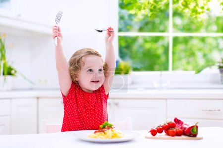 Photo for Kids eat pasta. Healthy lunch for children. Toddler kid eating spaghetti Bolognese in a white kitchen at home. Preschooler child cooking noodles with tomato and pepper for dinner. Food for family. - Royalty Free Image