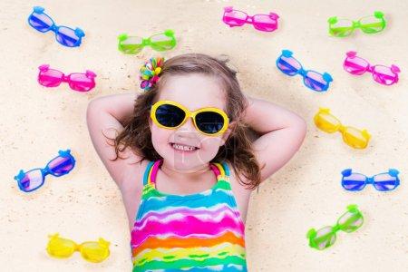 Photo pour Enfant, lunettes de soleil sur une plage. lunettes de soleil pour les enfants. petite fille à choisir des spectacles. lentille et choix de cadre coloré pour les enfants. protection anti-UV pour enfants. lunettes de sécurité pour des vacances tropicales. - image libre de droit