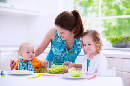 Photo for Young mother and two children cooking in a kitchen. Parent and kids cook dinner. Family with baby and toddler kid eat at home. Child preparing and eating vegetable lunch. Preschooler healthy nutrition - Royalty Free Image