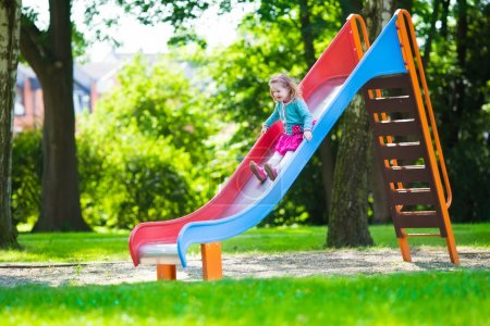 Photo pour Petite fille sur une aire de jeux. Enfant jouant dehors en été. Les enfants jouent dans la cour de l'école. Joyeux enfant à la maternelle ou à l'école maternelle. Les enfants s'amusent à la garderie. Tout-petit sur un toboggan . - image libre de droit