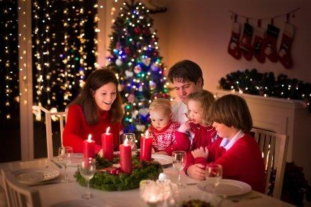 Photo pour Grande famille avec trois enfants célébrant Noël à la maison. Dîner de fête au foyer et à l'arbre de Noël. Les parents et les enfants mangent à la cheminée dans la chambre décorée. Bougie de couronne d'avent d'éclairage d'enfant . - image libre de droit