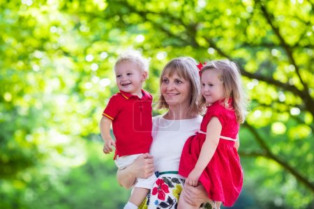 Mother holding two kids walking in summer park