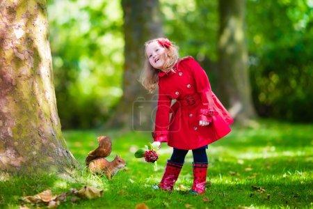 Little girl feeding a squirrel in autumn park