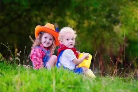 Little boy and girl dressed up as cowboy and cowgirl playing wit