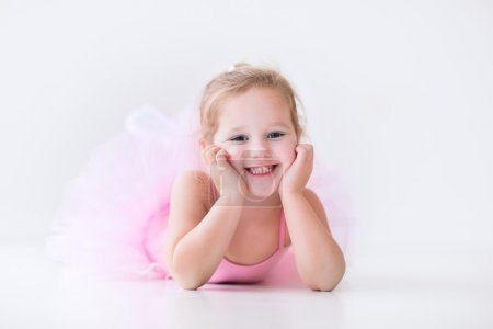 Photo for Little ballerina girl in a pink tutu. Adorable child dancing classical ballet in a white studio. Children dance. Kids performing. Young gifted dancer in a class. Preschool kid taking art lessons. - Royalty Free Image