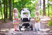 Children pushing stroller with newborn baby