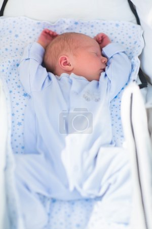 Newborn baby sleeping in white stroller