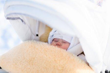 Photo pour Mignon nouveau-né dormant dans une poussette par une froide journée d'hiver. Le nouveau-né fait une sieste dans une poussette dans un parc enneigé. Les enfants dorment à l'extérieur dans un landau. Plaisir en famille dans la neige . - image libre de droit