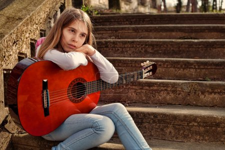 Pensive Teenage Girl Holding a Guitar in Her Lap Against Old Stone Stairs