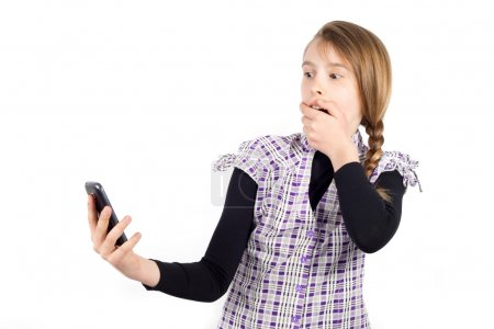 Girl Covering Her Mouth With Hand and Looking at the Screen of Cell Phone With Surprised Expression