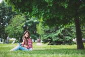 Mladá krásná žena mluví po telefonu v parku