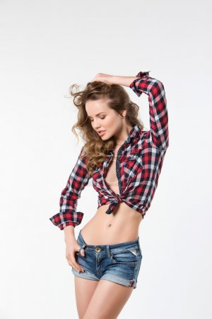 Portrait of sexy girl in checkered shirt and denim shorts. Beauty and Fashion.