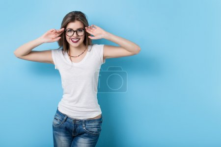 Photo for Young girl with glasses in a modern style on a background of a blue wall - Royalty Free Image