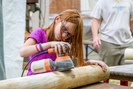 Teenage girl sanding the log