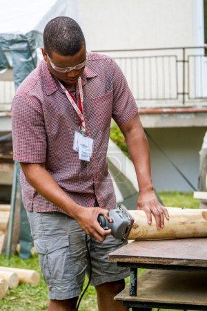Carpenter sanding the log