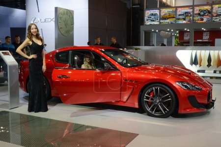 A young woman from the Maserati team. In the long black dress near car. Gran Turismo. Red Car. Moscow International Automobile Salon Premium