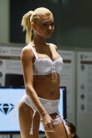 Photo for Moscow Traffic 5th International Exhibition of underwear, beachwear, home wear and hosiery Lingrie Expo Young blond woman in white lingerie and white stockings Flash Sexy Desire - Royalty Free Image