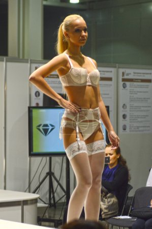 Photo for Moscow Traffic 5th International Exhibition of underwear, beachwear, home wear and hosiery Lingrie Expo Young blond woman in white lingerie and white stockings - Royalty Free Image