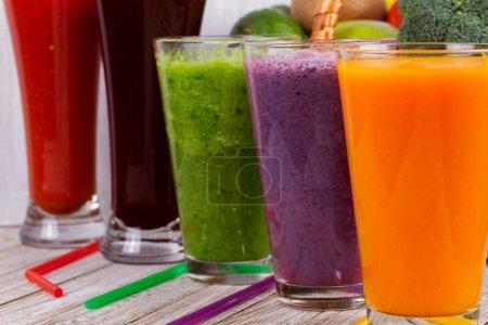 gesunde bunte Smoothies mit Obst und Gemüse vor rustikalem Holzhintergrund