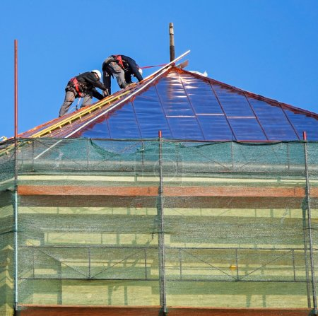 Roofers are working on the top of an old building