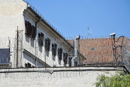 Prison building with barbed wire fence and security camera