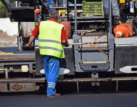 Construction worker next to an asphalt paving vehicle