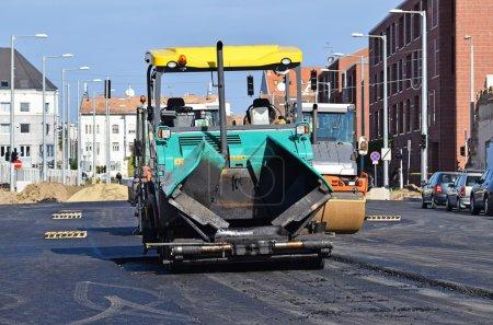 Asphalt paving vehicle at the road construction