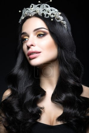 Beautiful dark-haired woman with a crown of precious stones, curls and evening makeup. Beauty face.