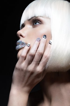 Elegant beautiful girl in a white wig, with the lips of rhinestones and festive manicure. Beauty face.