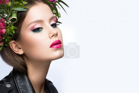 Beautiful girl with a lot of flowers in their hair and bright pink make-up. Spring image. Beauty face.